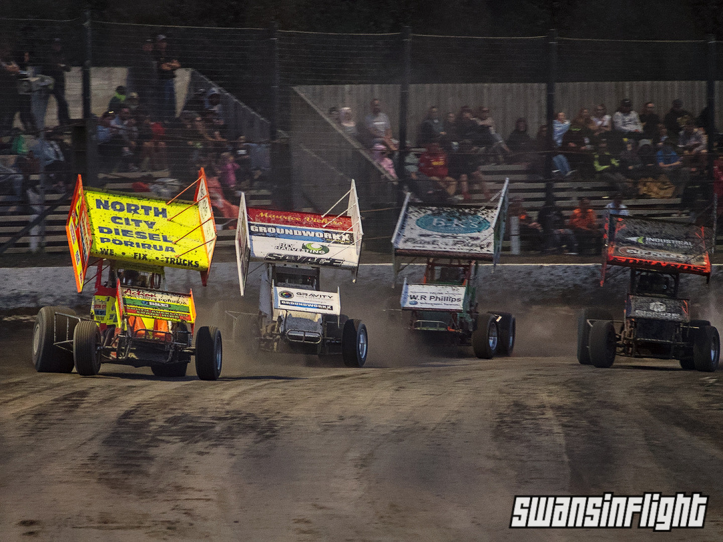 4 speedway sprintcars side by side, coming out of corner and towards the camera down the straight.